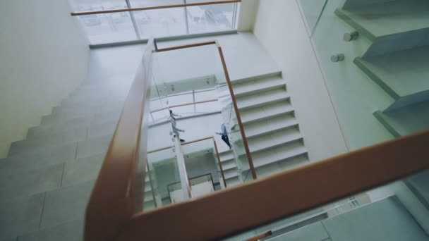 Top view of two businessmen meet at stairs in modern office center and talking while having break