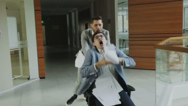 Slow-Motion Dolly erschossen von zwei verrückten Geschäftsleute Reiten Bürostuhl und kotzte Papiere und dabei Spaß in Lobby des modernen Business-center