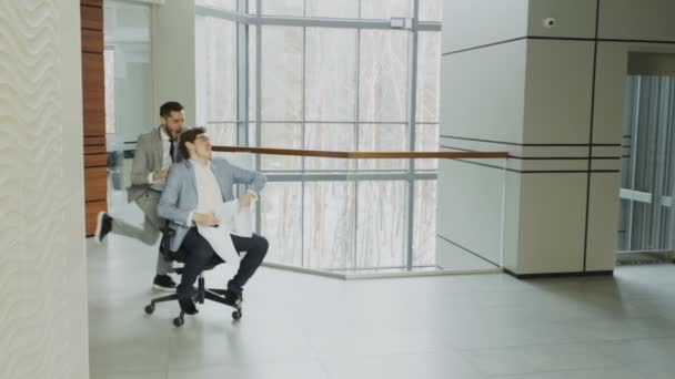 Slow motion of Two crazy businessmen riding office chair and throwing papers up while having fun in lobby of modern business center