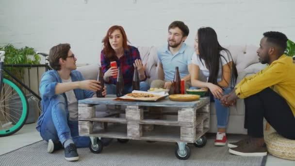 Gruppo di giovani amici multietnici parlare insieme e divertirsi pur avendo casa partito godendo al chiuso snack e birra