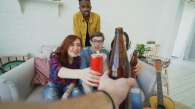 POV shot of male hand clinking beer bottle with friends while celebrating party at home indoors