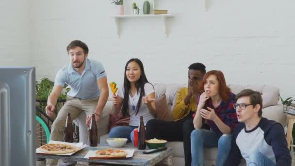 Slow-Motion von jungen Freunden gerade Olympischen Spiele Spiel am Tv zusammen Snacks zu essen und Bier zu trinken. Einige von ihnen zufrieden mit ihrer Mannschaft gewinnen aber andere enttäuscht