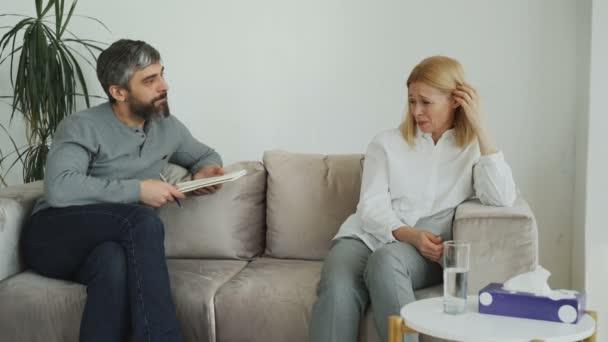 Muž zkušený psycholog mluví a uklidni se depresi Plačící žena pacient během psychoterapeutické sezení