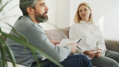 Adult woman talking while passing psychological test during visit to male psychoanalyst in office