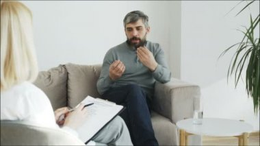 Stressed bearded man talking about his problems to psychologist in her office indoors