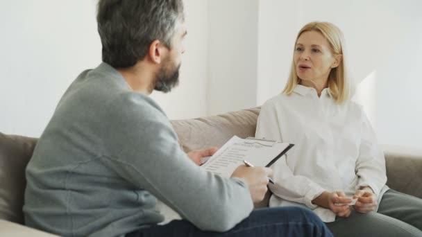 Dospělé ženy mluví při předávání psychologický test během návštěvy mužského psychoanalytik v úřadu