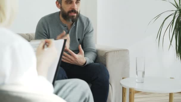 Tilt up of Angry man talking about his family porblems with female psychologist in her office indoors