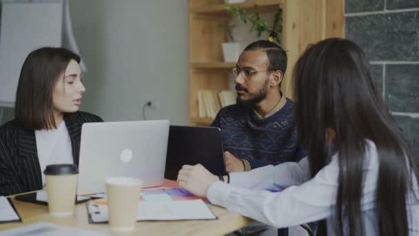 Skupina multi etnické podnikání mladých lidí sedí u stolu s notebooky pracovat a mluví o novém zahájení projektu v moderní podkrovní kanceláři