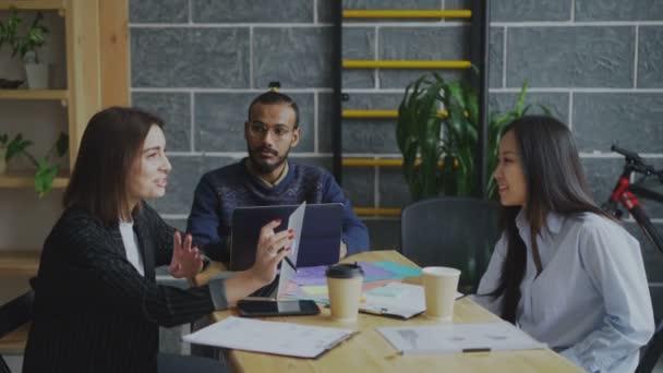 Více etnických mladý tým diskuse o nových projektových záměrů v moderní zahájení činnosti úřadu. Dva usmívající girs rozhovor a zároveň africké člověka naslouchání jejich disccussion