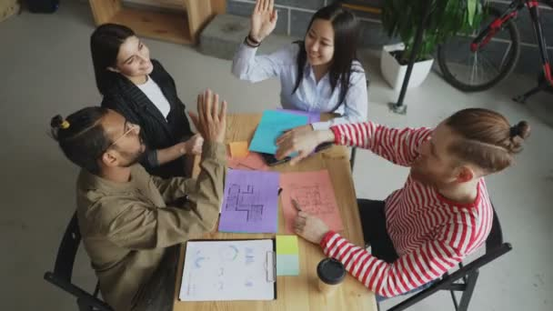 Top view of start-up business team of multi-ethnic coworkers giving high five all together sitting at table in office