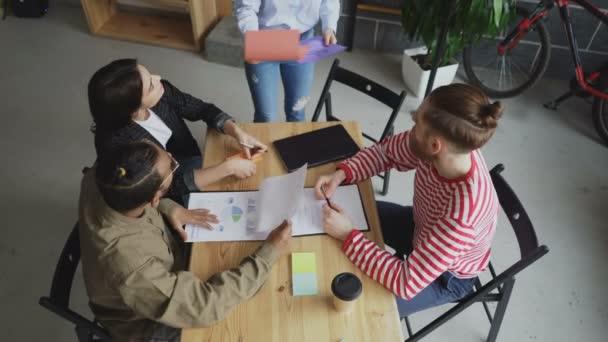 Vista superiore di giovane donna asiatica condivisione progetti architettonici con squadra multietnica e discutere nuove start-up progetto in ufficio moderno