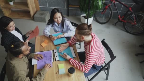 Pohled shora start-up firmy multietnické týmu sedí u stolu s projektové dokumenty a chatování během přestávky na kávu v útulné kanceláři