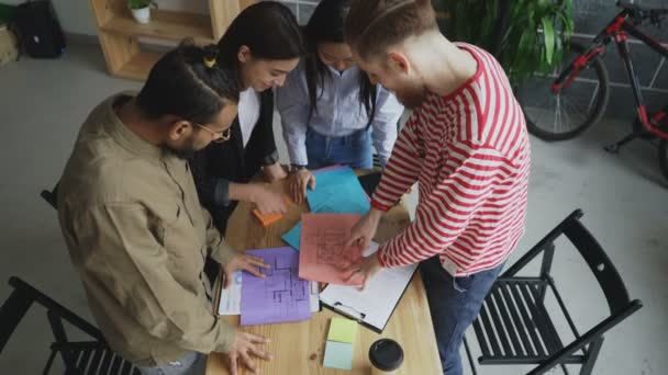 High angle view of Group of multiethnic young coworkers watching papers with building plan standing around table in office