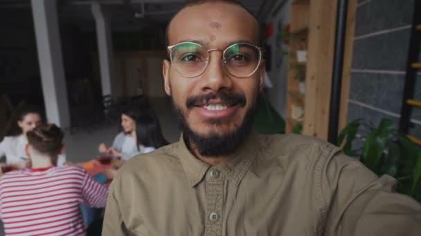 Detail z afrických amerických bokovky muž v brýlích držení smartphone a mají onlive video volání, zatímco jeho kolegové pracují v moderní kanceláři