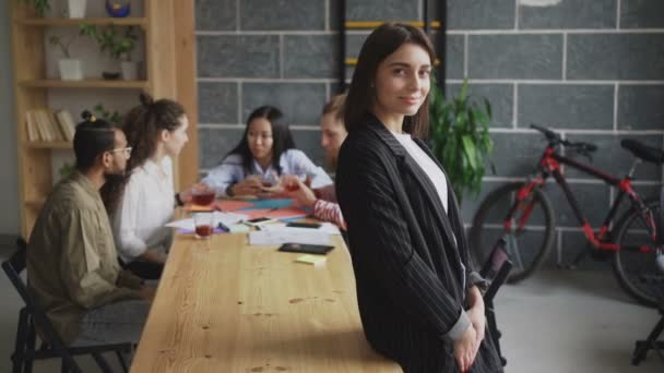 Portrait of young confident businesswoman looking at camera and smiling while her multi-ethnic team working on start-up project in modern loft office