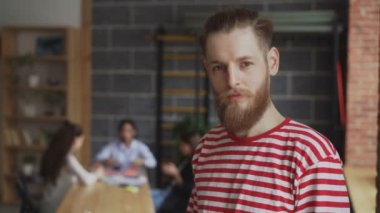 Portrait of young hipster businessman smiling and looking at camera while his colleagues working at modern loft office