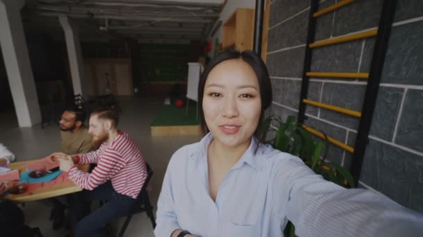 Cheerful asian woman holding smartphone and have onlive video call while her colleagues working in modern office