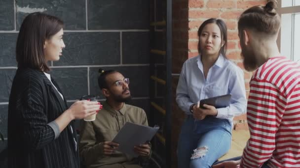 Group of multiracial colleagues disscussing startup project while standing near window in office with coffee and papers