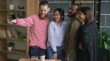 Happy multi-ethnic team taking selfie in modern loft office. Hipster man holding smartphone take self portrait with his colleagues