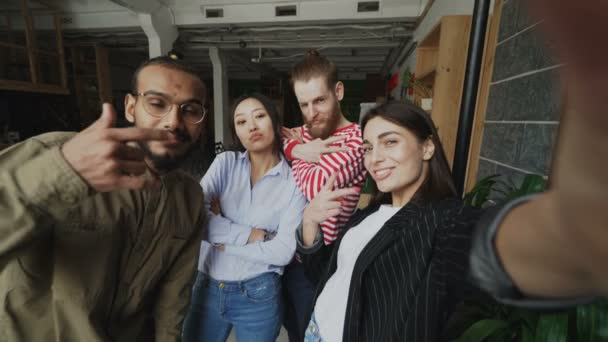 Point of view of happy multi-ethnic team taking selfie in modern loft office. Woman holding smartphone and take self portrait together with her colleagues