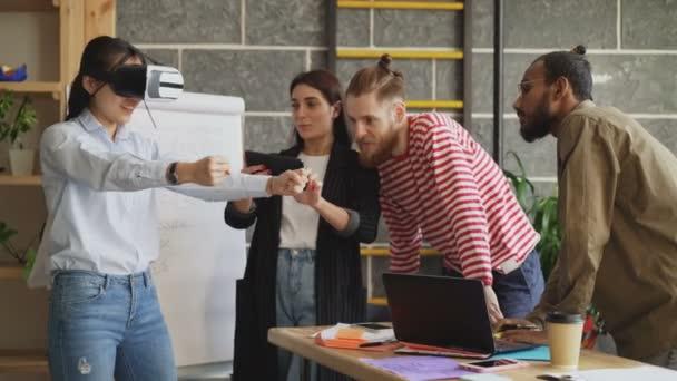 Asiatin testet neuen Rennspiel-Simulator auf vr-Headset mit Kollegen, die ihre Erfahrungen mit digitalem Tablet im Start-up-Büro kontrollieren