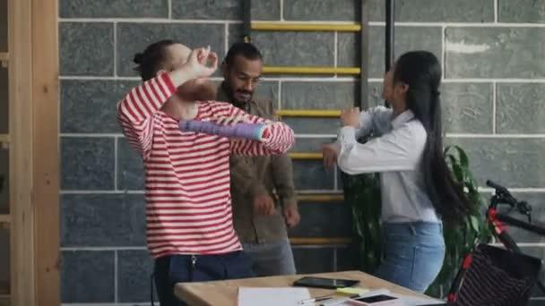 Rozmanité multietnické start-up obchodní tým bavit tancem v podkroví úřadu a slaví úspěch projektu