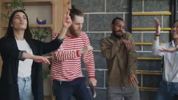 Diverse group female and male start-up business team have fun dancing in modern office and celebrating success of project