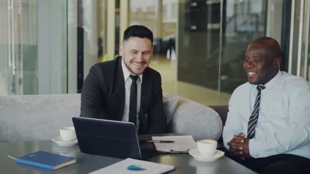 Two multi ethnic businessmen looking at laptop computer and laughing in glassy cafe. Business collaegues having fun and joking