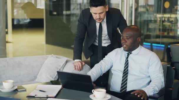 Confident african ceo gives guidelines to bearded caucasian manager in business suit standing nearby in modern cafe. African American businessman sits pointing at his laptop computer