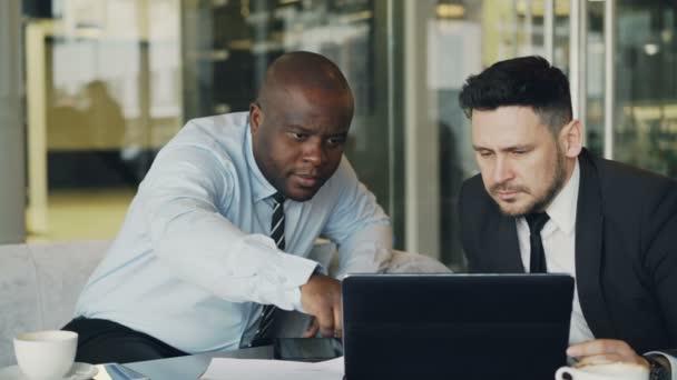 Két munkatárs látszó-on laptop számítógép, és megvitatni a projektjeik modern irodai üveg falak. Szakállas üzletember és társa asztalnál ült és beszélt