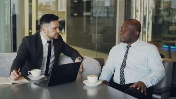 Due uomini daffari fiduciosi, discutendo sulla partnership durante la riunione nella moderna caffetteria vetroso