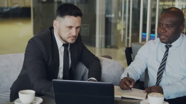 Ambitious businessmen discussing startup project in modern glassy lobby. African American entrepreneur writing in notebook and his caucasian partner in business suit pointing at laptop computer