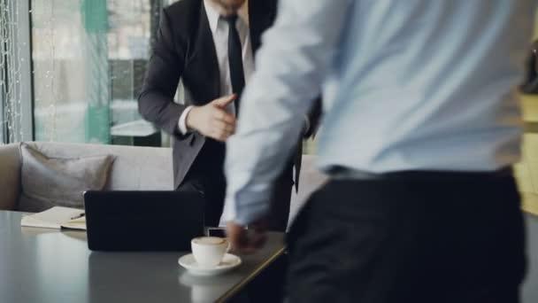 7dc8a14e3393 Δύο businessmaen σε επίσημα ρούχα χειραψία και λαμβάνοντας καθίσματα για  πολυθρόνες λευκό δέρμα να συζητήσουν τους startup επιχείρηση snazzy καφέ–  πλάνα ...