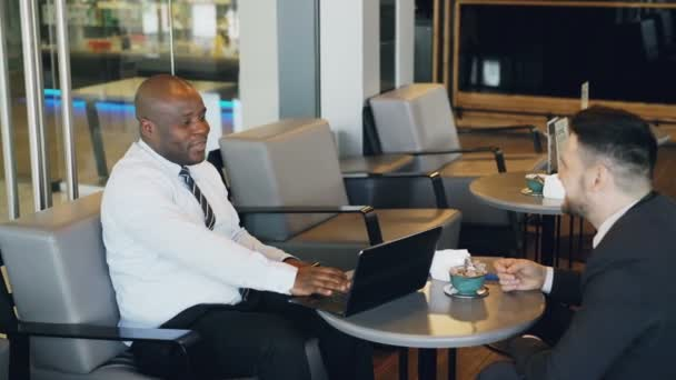 Two multiracial businessmen in formal clothes smiling, gesturing and discussing their startup in spacious cafe during lunch break. Advanced laptop is on their table.
