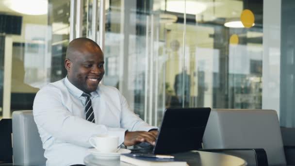 Veselé americký podnikatel s úsměvem, tisk a pracuje na svém notebooku v kavárně sklovité během polední přestávky. Ukazuje se tvářili se šťastně gesto Ano