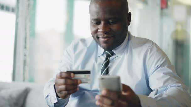 Vidám afro-amerikai üzletember, hivatalos ruhák fizet online számla hitelkártya és smartphone tartva kezében üveges kávézó