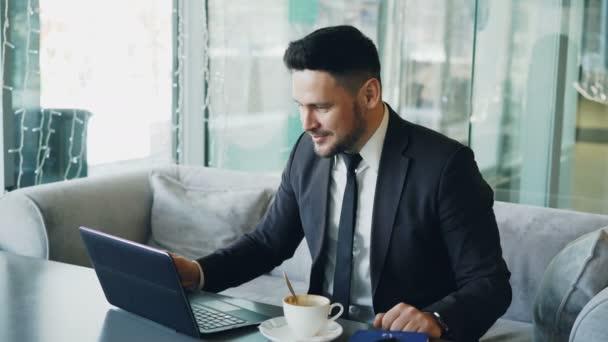 Kaukázusi üzletember alaki ruhák beszélgető keresztül webkamera laptop, és intett a kezével boldogan egy ízléses kávézó ebédre idő alatt.