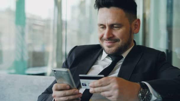 Boldog kaukázusi üzletember hivatalos ruhát fizet online számla vezetése hitelkártya és smartphone a kezében üveges kávézóban során ebédszünet