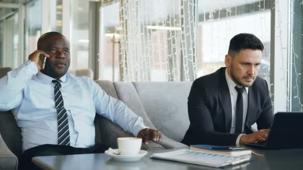 Caucasian businessman in formal clothes printing business information on his laptop and his African American colleague talking on smartphone in cafe.