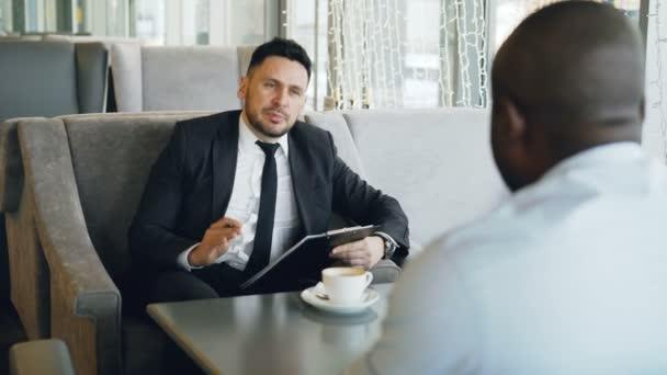 Jistý bělošský podnikatel ve formálním oblečení s pracovní pohovor s jeho africké americké zaměstnance v sklovité café během polední přestávky.