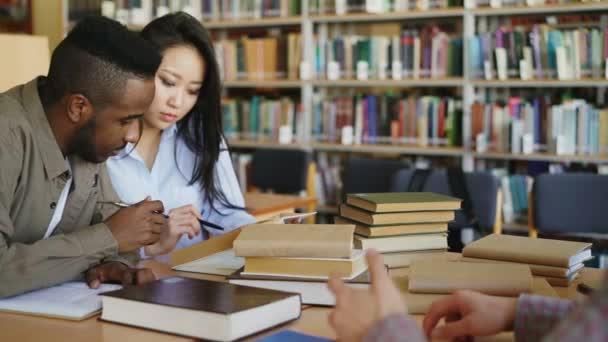 Mladí africké americké a asijské vysokoškoláci pracují společně připravují na zkoušky, zatímco sedí u stolu v univerzitní knihovně se spolužáky