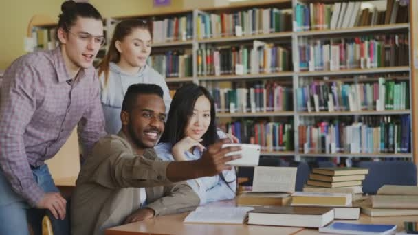 Skupina zahraničních studentů bavte se usmívá a fotí selfie na fotoaparát smartphonu v univerzitní knihovně. Veselí přátelé mají odpočinku při připravit na vyšetření