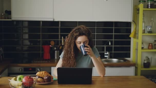 young attractive curly happy caucasian woman is sitting in kitchen working on laptop drinking tea, her husband comes and she shows something in laptop