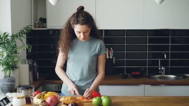 fröhliche Frau, die in der Küche das Frühstück zubereitet, ihr Mann kommt mit Äpfeln und zeigt ihr Jonglieren, Frau lacht, ein Apfel fällt und Paar sucht Apfel