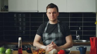 Portrait of young handsome caucasian executive chef in apron sitting at table in modern lighty spacious kitchen, smiling, he is calm and positive, looking at camera