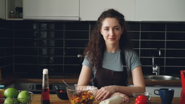 Portrait of young caucasian executive chef woman in apron sitting at table in modern lighty spacious kitchen, smiling,calm and positive, looking at camera