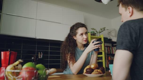 mladý bělošský pár sedí u stolu v moderní kuchyni doma dicussing něco, kudrnaté ženy sedí zpět do kamery pít čaj a jíst croussant, drží šálků
