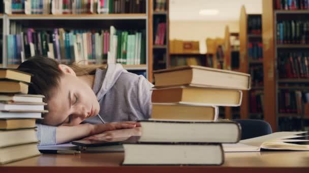 Mladé krásné kavkazské studentka spí na stole, obklopen hromadami knih a dokumentů, telefon je lhaní před ní, ona je velké univerzitní knihovny