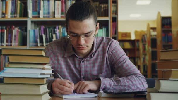 Szép tizenéves fiatalember szemüveg számítások a copybook az egyetemi könyvtár gondolkodás asztalnál ül. Ő keres el és tömör witing thoughtfuly