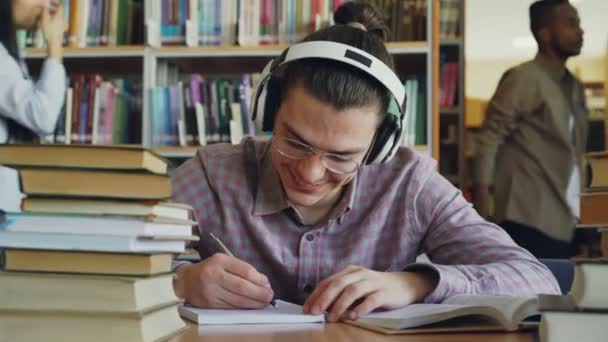 Young handsome caucasian schoolboy sitting at table in big school library is writing something in copybook. He is smiling and looks positive and happy, books lying on table